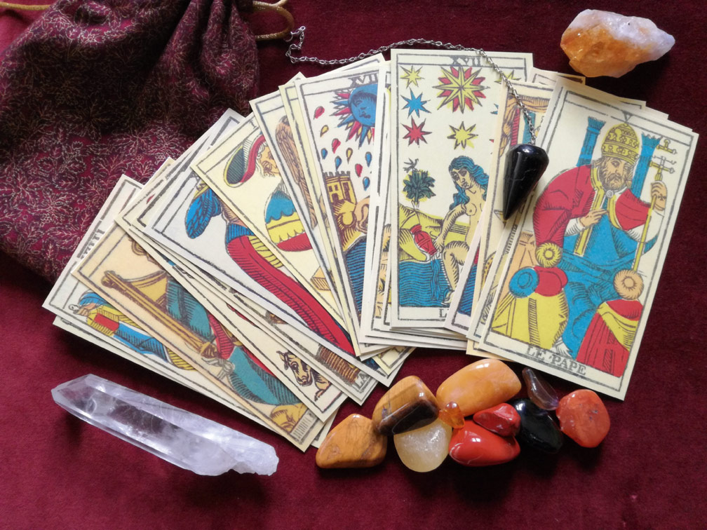 tarot cards, crystals and pendulum; some of the tools of psychic readings